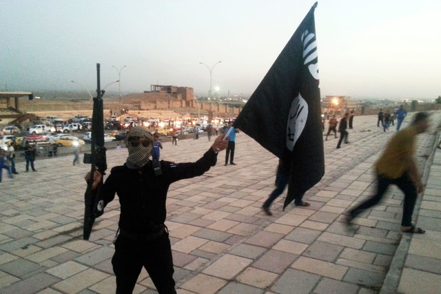 A fighter of the Islamic State of Iraq and the Levant (ISIL) holds an ISIL flag and a weapon on a street in the city of Mosul, June 23, 2014. Islamic State urged its followers on Monday to attack  ...