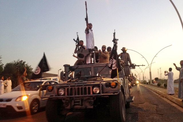 Fighters from the Islamic State group parade in a commandeered Iraqi security forces vehicle down a main road in the northern city of Mosul, Iraq, Monday, June 23, 2014. The spokesman of the Islam ...