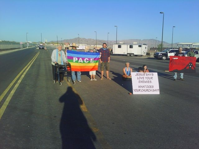"Anti-drone demonstrators hold a ""pace"" banner, Italian for ""peace."" Four anti-drone protesters were cited for blocking a road at Creech Air Force Base, 45 miles northwest of Las Vegas, on Monday,  ..."