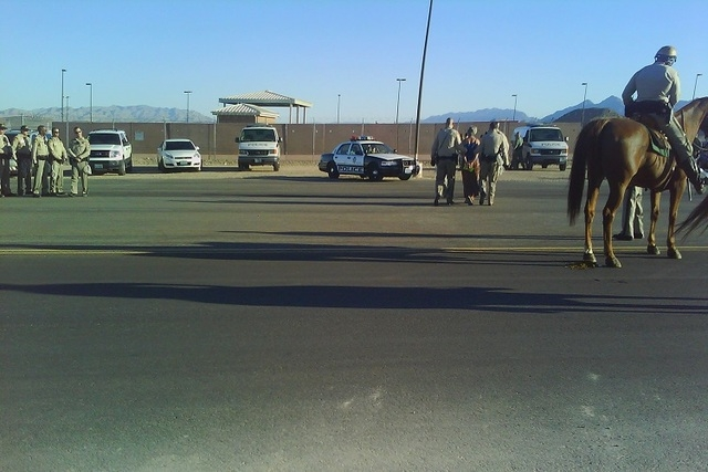 Las Vegas police escort one of four anti-drone protesters who were cited for blocking a road at Creech Air Force Base, 45 miles northwest of Las Vegas, on Monday, Sept. 22, 2014. (Marcus Page-Coll ...