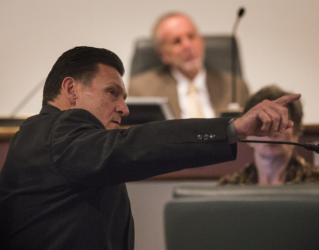 Suspended Family Court Judge Steven Jones points to a photo during a Nevada Commission on Judicial Discipline hearing at Las Vegas Convention Center Boardroom on Thursday, Dec. 5, 2013. The photo  ...