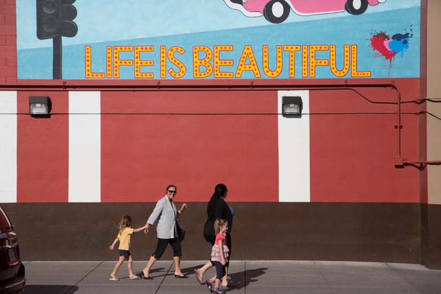 Tami Belt (in grey) walks with her friend Krista Whitley-Castellarin, and Mia and Bella, Whitley-Castellarian's daugthers, in front of a mural painted for the inaugural Life Is Beautiful Festival  ...