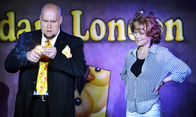 """Audience member Fontella Powell, right, watches as comedy magician Adam London appears to destroy her ring during a performance of """"Laughternoon"""" at the D Showroom in the D hotel-casino  ..."""