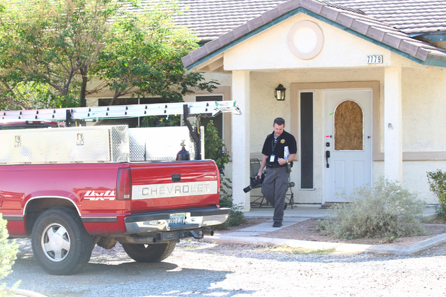 A crime scene investigator on Wednesday, Sept. 17, 2014, leaves 7779 Maverick St. in Las Vegas where a 15-year-old boy fired a shotgun from outside into the house door on Tuesday, Sept. 16, 2014.  ...