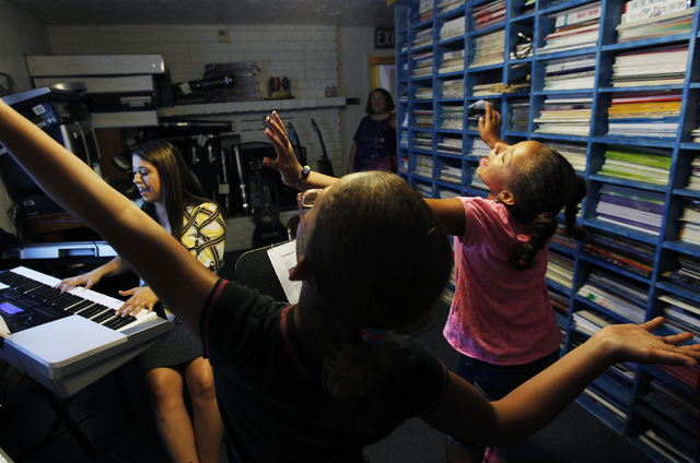 Instructor Megan Schnizlein, left, gives Shylin Thompson, middle, and Faith Miller-Hooks a singing lesson at The Rockin' Music Zoo in Las Vegas on July 31, 2014. Music Director Bonnie Fitch is see ...
