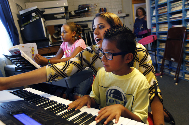 Instructor Megan Schnizlein, middle, gives George Miller-Hooks, right, and Faith Miller-Hooks, left, a piano lesson at The Rockin' Music Zoo in Las Vegas on July 31, 2014. Music Director Bonnie Fi ...