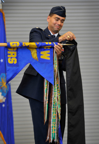 Lt. Col. Gregory Wintill, outgoing commander of the 65th Aggressor Squadron, covers up the squadron's flags during a inactivation ceremony at Nellis Air Force Base on Friday, Sept. 26, 2014. The s ...