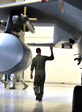 A member of the United States Air Force who choose not to give his name, touches the underbelly of a F-15 Eagle after the inactivation ceremony for the 65th Aggressor Squadron at Nellis Air Force  ...
