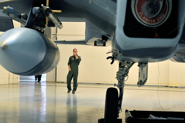A member of the United States Air Force who choose not to give his name, takes a final look at an F-15 Eagle after the inactivation ceremony for the 65th Aggressor Squadron at Nellis Air Force Bas ...