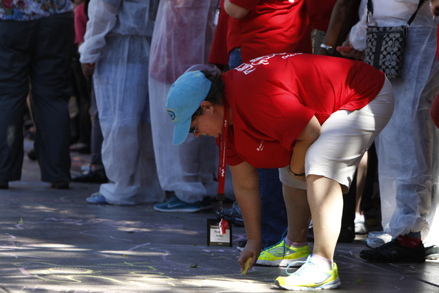 Registered nurse Paulette Edwards writes a message on the sidewalk using chalk during a rally and march by the California Nurses Association/National Nurses Organizing Committee on the Strip near  ...