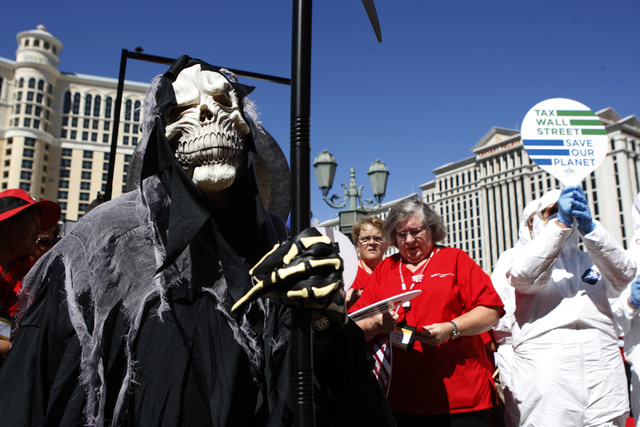 Communications employee Martha Wallner as grim reaper, stands on the Strip near Planet Hollywood casino-hotel during a rally and march by the California Nurses Association/National Nurses Organizi ...