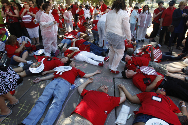 Registered nurses and health workers with the California Nurses Association/National Nurses Organizing Committee lay down on the ground to represent the lives lost from infectious diseases around  ...