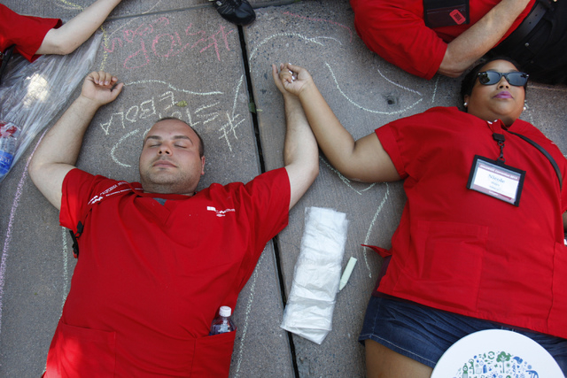 Registered nurses Gevorg Adjian, left, and Nicole Mayo, lay down on the ground to represent the lives lost from infectious diseases around the world during a rally and march hosted by the Californ ...