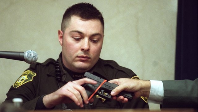 Metro Police officer Brian Yant is handed a weapon during  a court hearing on January 3, 2002. (Clint Karlsen/Las Vegas Review-Journal file)