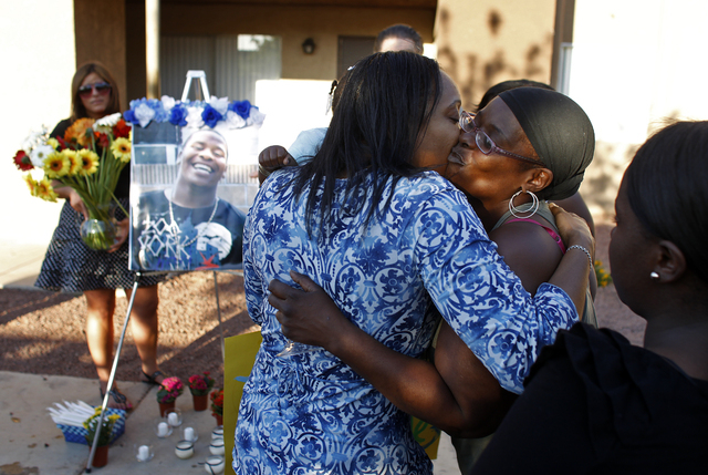 JOHN LOCHER/LAS VEGAS REVIEW-JOURNAL Kimeryn Williams, left, gets a kiss from Trenia Cole during a vigil for Trevon Cole Friday, June 10, 2011 outside of the apartment where he was killed in Las V ...