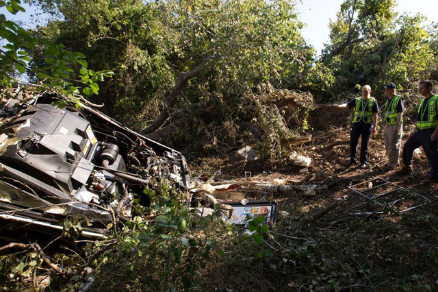 Investigator-in-charge Jennifer Morrison, left, and NTSB Board Member Robert Sumwalt, center, view the wreckage of a bus crash near Davis, Oklahoma, in this undated handout photo provided by the N ...