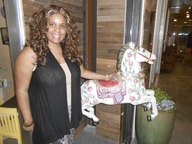 Stephanie Mitchell-Anthony pauses by the carousel horse outside her shop, Pas De Deux Children's Couture, which opened June 6, 2014, in the Market LV at Tivoli Village, 420 S. Rampart Blvd. She  ...