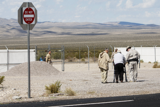 Steve Kelly, left, and a Wackenhut security guard assist Jerry Zawada toward a holding pen at the Nevada National Security Site during a civil disobedience action marking the United Nations Intern ...