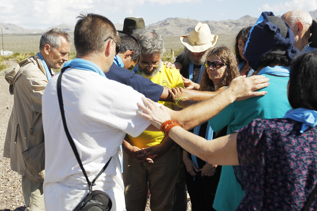 Anti-nuclear weapons demonstrators say a blessing outside the Nevada National Security Site during a civil disobedience action marking the United Nations International Day of Peace Sunday, Sept. 2 ...
