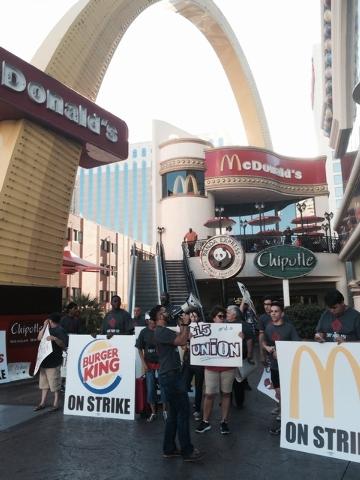 AJ Buhay, center, of Progressive Leadership Alliance of Nevada (PLAN) shouts slogan outside McDonald's on Las Vegas Blvd across The Mirage on the Strip. (Bizu Tesfaye/Las Vegas Review-Journal)