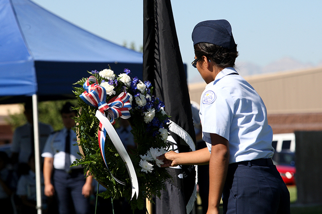 An Air Force Junior ROTC cadet from Rancho High School place a daisy in a wreath during a ceremony Friday, Sept 19, 2014, at Nellis Air Force Base to remember prisoners of war and those missing in ...