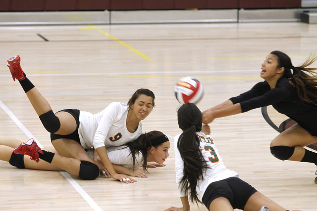 From left, Mojave Girls Volleyball players Allison O'Neill, RayEna Rael and Leilani Limtiaco crash to the floor as Sierra Cummings dives in to dig the ball during their game against Faith Lutheran ...