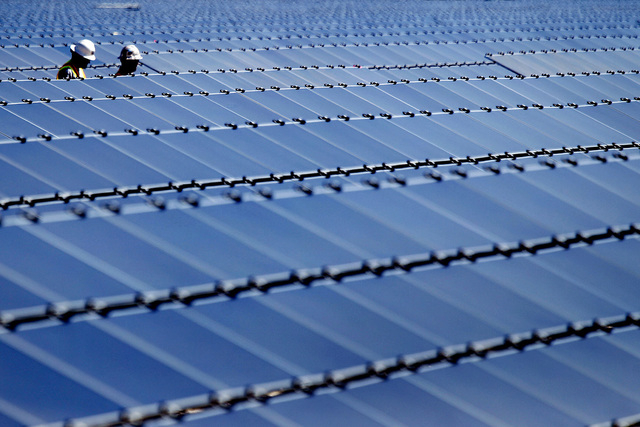 Two men walk along rows of solar panels at Silver State North, a photovoltaic power station project in Ivanpah Valley, on Tuesday, Sept. 20, 2011. Silver State South will surround an existing, 600 ...