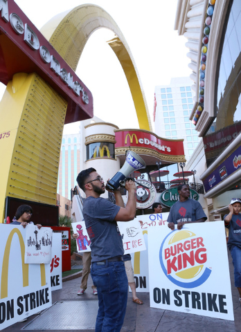 AJ Buhay of Progressive Leadership Alliance of Nevada (PLAN) shouts slogans as he protests with workers from restaurants including McDonald's, Burger King, Wendy's and KFC, outside McDonald's near ...