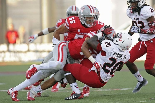 UNLV Rebels defensive back Torry McTyer, center, and UNLV Rebels linebacker Tau Lotulelei (55) tackle Northern Illinois tail back Keith Harris (20) in the first half of their NCAA Football game at ...