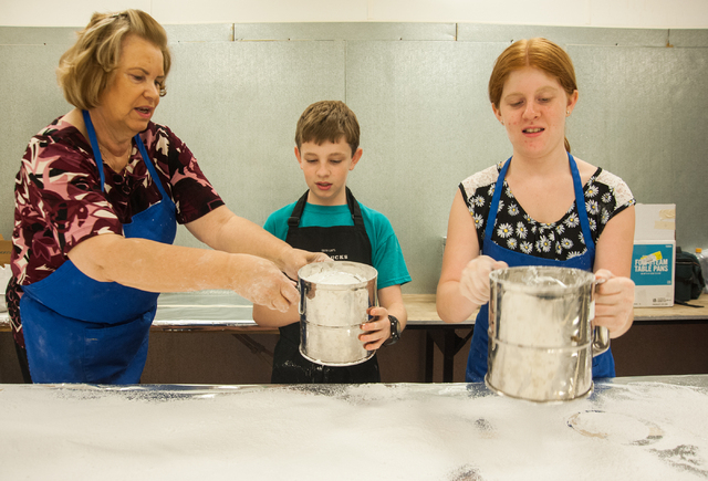 Volunteers from left, Geri Kypreos, Luke Marossy, 10, and Samantha Zondiros, 12, sifts through powdered sugar as part of a collaboration to bake greek cookies for the upcoming Greek Food Festival  ...