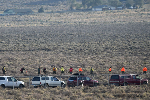 Officials comb the area where a plane crashed and the pilot died on the race course while attempting to qualify for the Reno National Championship Air Races in Reno, Sept. 8, 2014. This is the sam ...