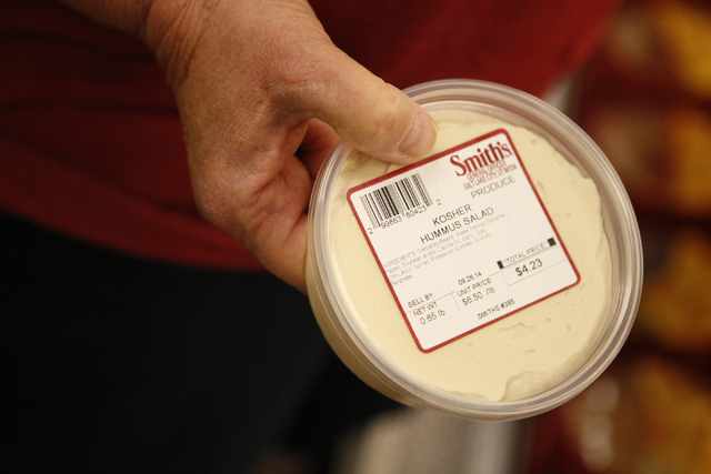 Linda Tohn waits in line holding kosher hummus as she orders round challah bread for Rosh Hashanah, the Jewish new year, at Smith's, 2211 N. Rampart Blvd., in Las Vegas Thursday, Sept. 18, 2014. ( ...