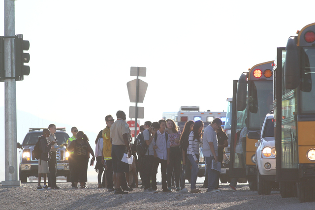 Students involved in a school bus crash, which included another vehicle, board another bus as Nevada Highway Patrol officers respond at the 215 Beltway and Lamb Boulevard intersection in North Las ...