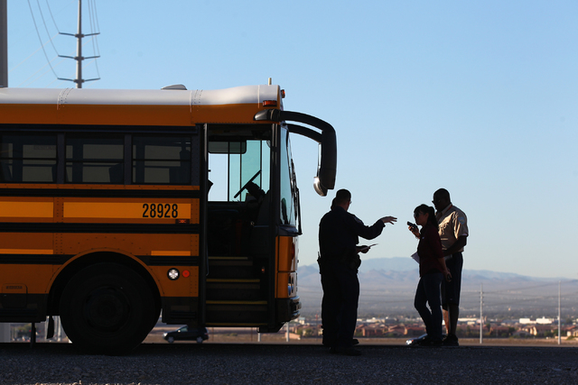 Nevada Highway Patrol officers investigate a crash involving a school bus which was carrying around 50 children and another vehicle at the 215 Beltway and Lamb Boulevard intersection in North Las  ...