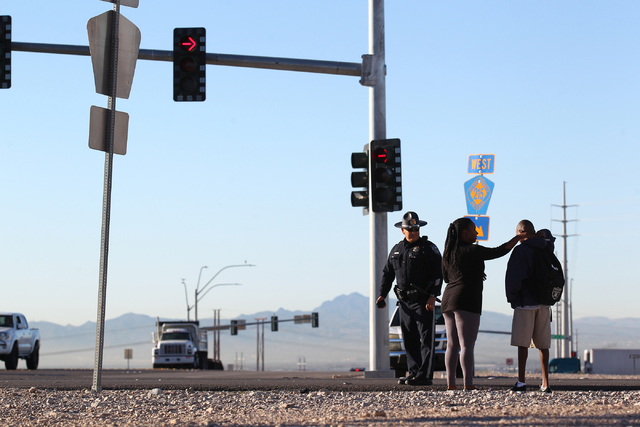 The mother of a student involved in a school bus crash, which included another vehicle, arrives as Nevada Highway Patrol officers and Las Vegas Fire and Rescue officials respond at the 215 Beltway ...