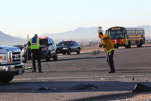 A Nevada Highway Patrol officer and Las Vegas Fire and Rescue official clean up debris while responding to a crash involving a school bus which was carrying around 50 children and another vehicle  ...
