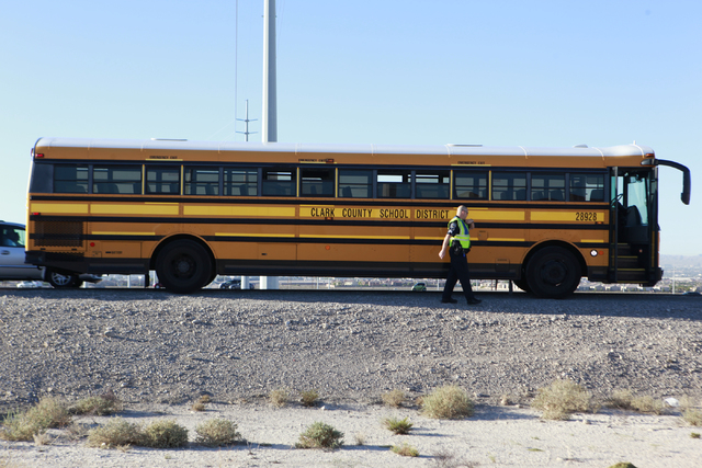Nevada Highway Patrol officers respond to a crash involving a school bus which was carrying around 50 children and another vehicle at the 215 Beltway and Lamb Boulevard intersection in North Las V ...