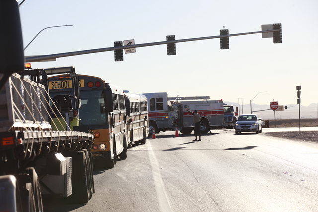 A Nevada Highway Patrol officer and Las Vegas Fire and Rescue officials respond to a crash involving a school bus which was carrying around 50 children and another vehicle at the 215 Beltway and L ...