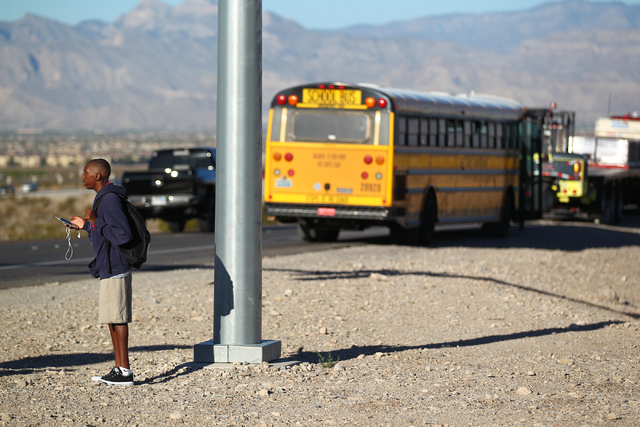 A student involved in a school bus crash, which included another vehicle, waits to be picked up as Nevada Highway Patrol officers and Las Vegas Fire and Rescue officials respond at the 215 Beltway ...