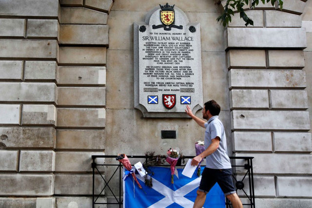A man touches the memorial of William Wallace, who led the Scottish rebellion against Edward I, in Smithfield, London, Thursday, Sept. 18, 2014. Polling in the referendum on Scottish independence  ...