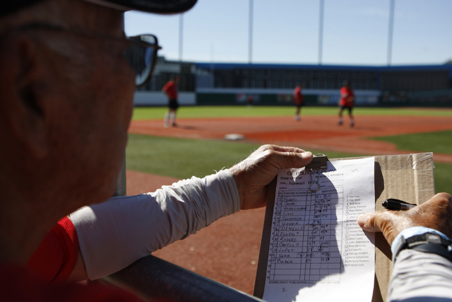 Hawaii Seniors John Nakamura (15) looks at his team's roster during their seeding game against Scrap Iron in the Las Vegas Senior Softball Association World Masters Championship at Crosley Field a ...