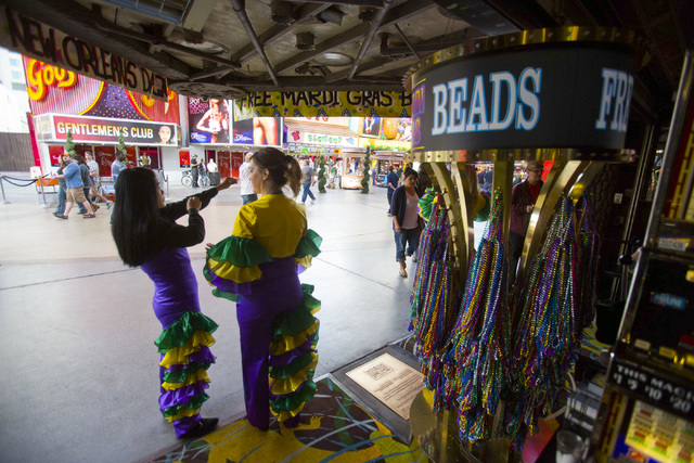 Two women hand out beads at La Bayou casino at the Fremont Street Experience on Thursday. (Jeff Scheid/Las Vegas Review-Journal)