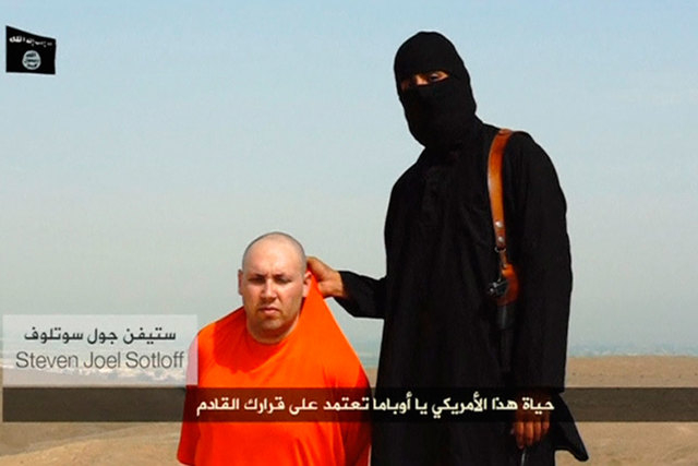 A masked Islamic State militant speaks next to a man purported to be U.S. journalist Steven Sotloff at an unknown location in this still image from an undated video posted on a social media websit ...