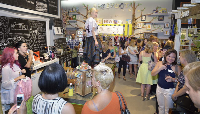 Shannon D'Errico, standing on counter, models one of the outfits designed by Huilin Chen, lower left, during a reception and auction of Chen's designs at ARTIFACT in Town Square Las Vegas. (Bill H ...