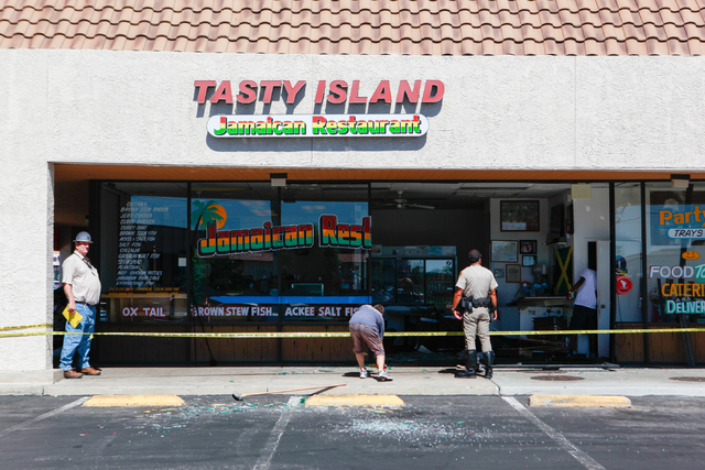 People survey damage from an SUV crash at Tasty Island Jamaican Restaurant, 6820 W. Flamingo Road, in Las Vegas on Wednesday, Sept. 24, 2014. The crash occurred at around 9:30 a.m. before the rest ...