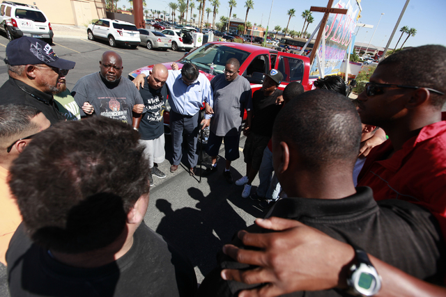 Faith-based leaders and members pray before a Las Vegas police press conference on Monday, Sept. 29, 2014, about 16-year-old Jose Hernandez Peña who was killed in a drive-by shooting at the Sahar ...