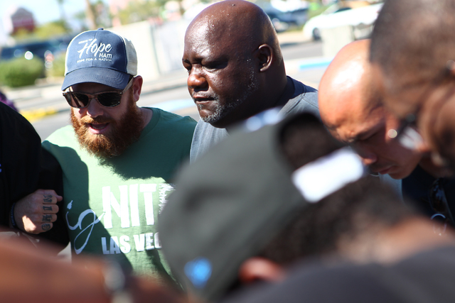Pastor Donnie Grinnell, left, prays with a group before a Las Vegas police press conference on Monday, Sept. 29, 2014, about 16-year-old Jose Hernandez Peña who was killed in a drive-by shooting  ...