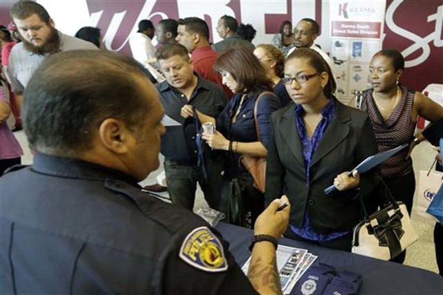 In this photo taken Tuesday, Aug. 19, 2014, job seeker Migdalia Feliz, of Miramar, Fla., third from right, listens to detective William DeJeus, left, of the Fort Lauderdale Police Department, at a ...