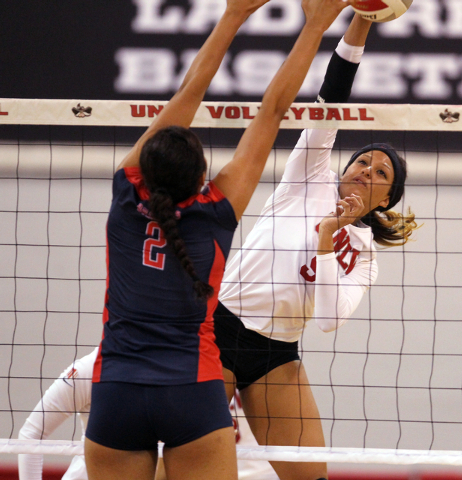 UNLV's Bree Hammel spikes past Lauren Torres of Fresno State in the third set of a volleyball game at Cox Pavilion in Las Vegas Thursday, Sept. 25, 2014. UNLV went on to beat Fresno State 3-0. (K. ...