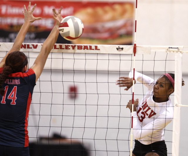 UNLV's Daryn Glenn (13) spikes past Brooke Legaux (14) of Fresno State in the third set of a volleyball game at Cox Pavilion in Las Vegas Thursday, Sept. 25, 2014. UNLV went on to beat Fresno Stat ...